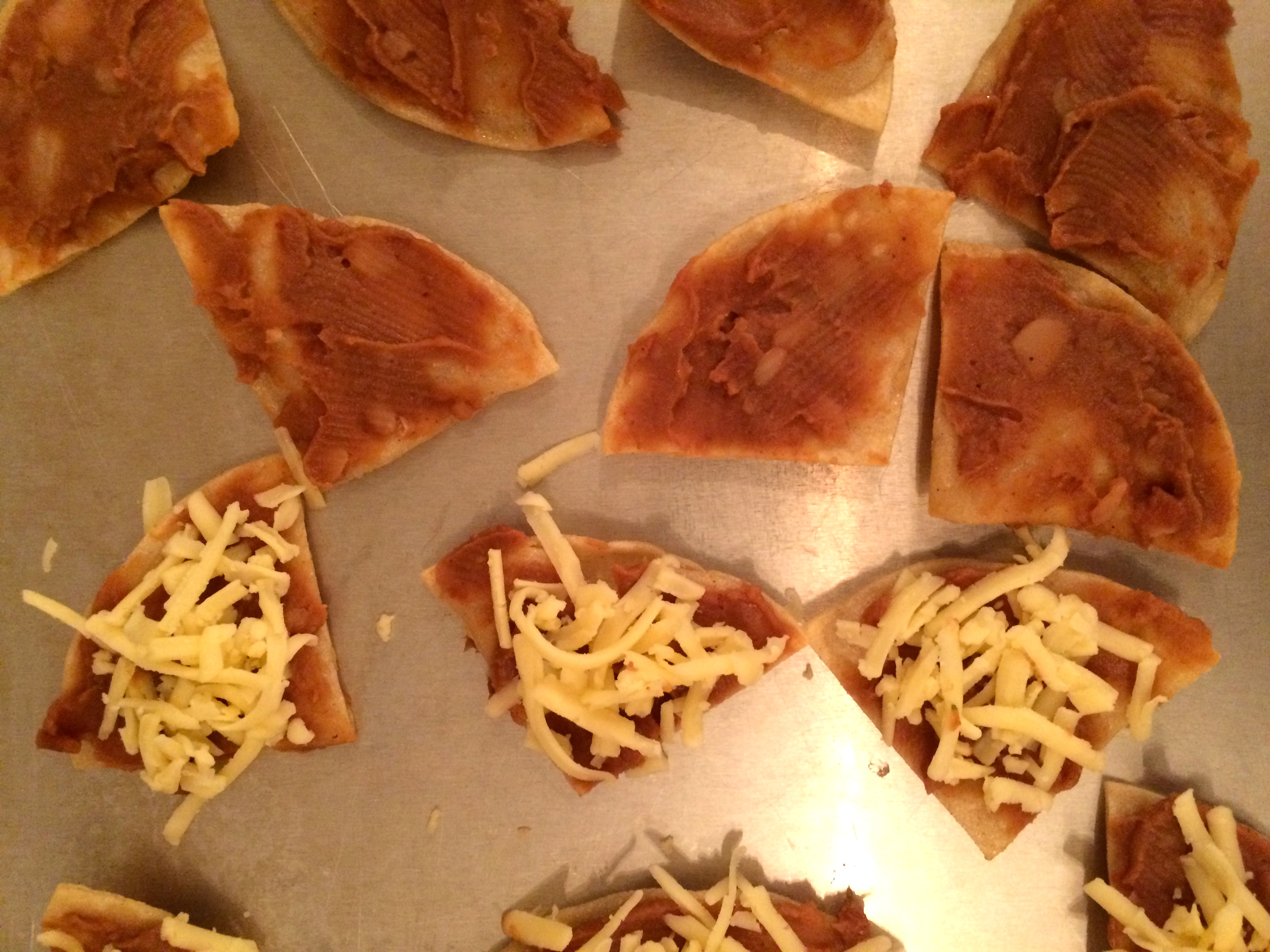 Tortillas on baking sheet with beans and cheese 2